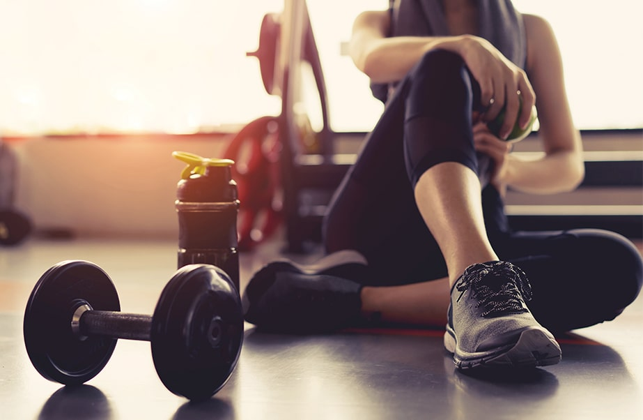 Woman sitting in Bayso Fitness Center with weights
