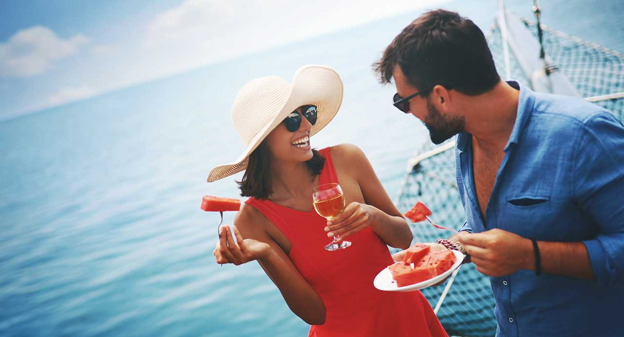 couple drinking and eating watermelon on a boat in the sarasota bay